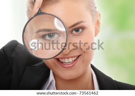 Young attractive smiling business woman looking into a magnifying glass. - stock photo