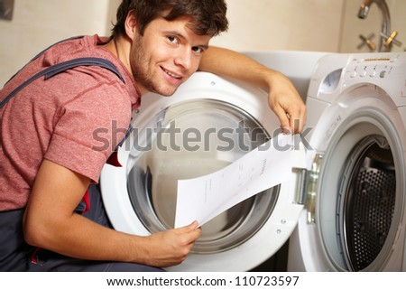 Young attractive smiling worker in uniform fixing washing machine, background - stock photo