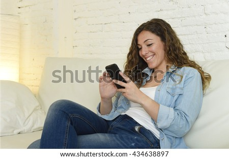 young attractive spanish woman in denim casual clothes using mobile phone app or texting on home sofa couch at living room enjoying happy and calm in internet social network and communication concept - stock photo
