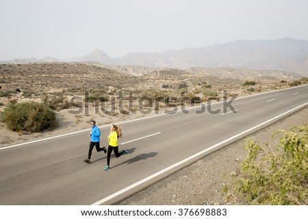 young attractive sport couple of man and woman running together on asphalt road  desert mountain landscape background looking happy and healthy in team training workout , fitness and wellness concept - stock photo