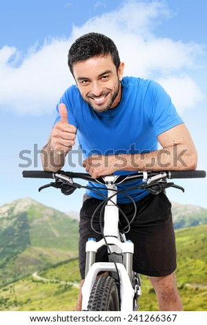 young attractive sport man riding mountain bike giving thumb up in fitness and healthy lifestyle concept wearing running clothes on spring or summer mountains landscape with blue sky - stock photo