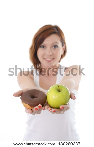 Young attractive sport Woman smiling and holding Apple and Chocolate Donut in Hands in healthy versus junk food dessert choice isolated on White background - stock photo