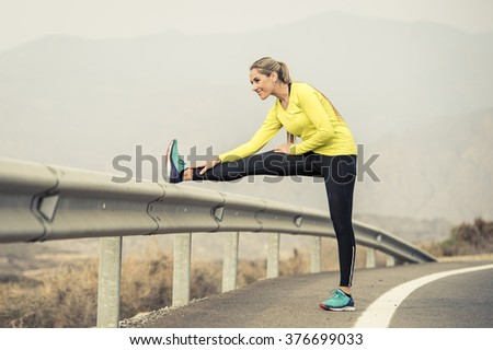 young attractive sport woman stretching leg muscle after running workout on asphalt road with dry desert landscape background in hard fitness training session and healthy lifestyle concept - stock photo