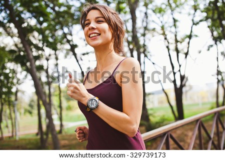 Young attractive sporty smiling woman running in forest wearing sport gadget pulse meter running tracker on wrist side view with copy space - stock photo