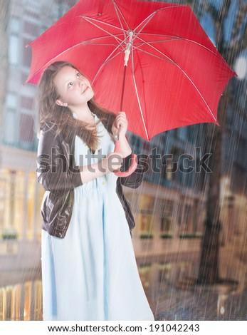 Young attractive teenage girl standing in rain with red umbrella. - stock photo
