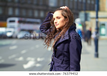 young attractive thoughtful female in city centre location, outdoor shoot - stock photo
