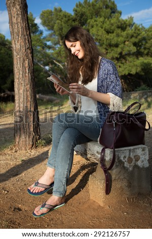 Young attractive tourist woman sitting and relaxing on a stone bench in a green park with sightseeing activities, reading a travel guide book. Travel and lifestyle outdoors. - stock photo