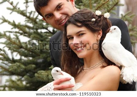 Young attractive wedding couple with pigeons pair, broom and bride over park autumn outdoor - stock photo