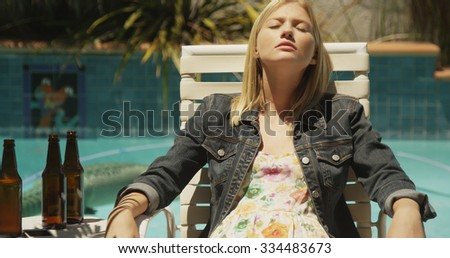 Young attractive white girl drinking by the pool - stock photo