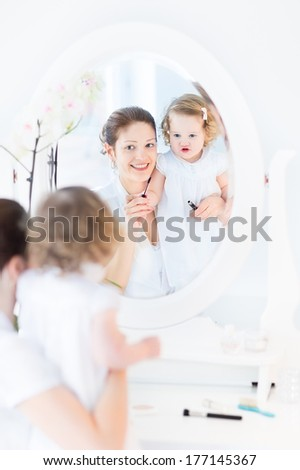 Young attractive woman and her cute funny toddler daughter wearing white dresses applying make up and cosmetics with a brush sitting in front of a round mirror in a white sunny bedroom  - stock photo