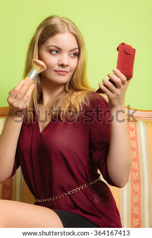 Young attractive woman applying make up with powder brush. Pretty gorgeous girl sitting on vintage retro sofa couch. Fashion and makeup. - stock photo