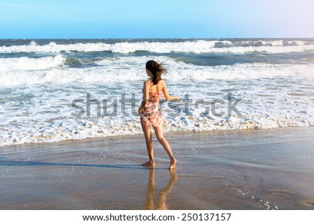 Young attractive woman dancing on the beach - stock photo