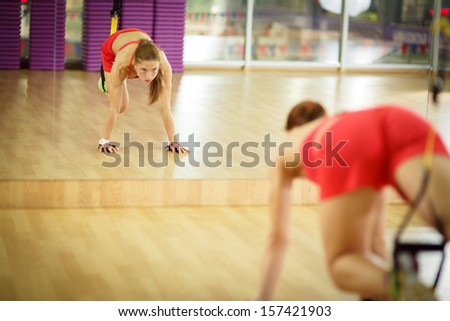 Young attractive woman does crossfit core abs training with trx fitness straps in the gym's studio, reflected in mirror - stock photo