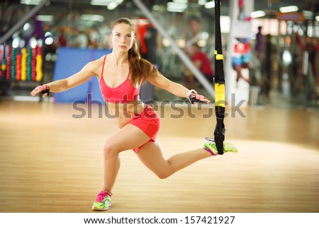Young attractive woman does crossfit lunge with trx fitness straps in the gym's studio - stock photo