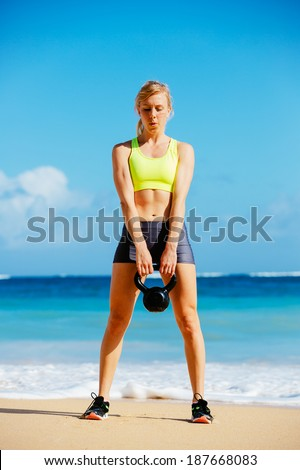 Young attractive woman doing kettle bell exercises outside. Fitness woman working out at the beach. Crossfit exercise. Fitness Concept. - stock photo