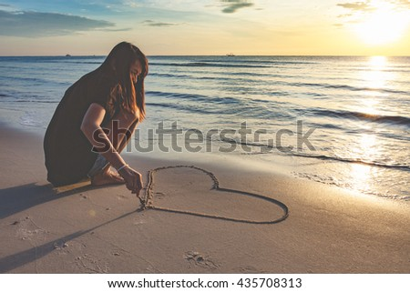 Young attractive woman drawing a heart in the sand on a tropical beach. - stock photo