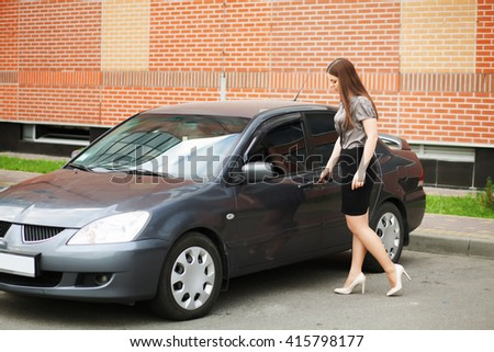 Young, attractive woman driving a car, going home from work - stock photo