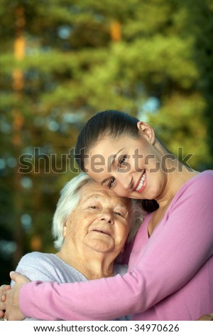 Young attractive woman embracing senior lady - stock photo