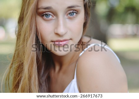 Young attractive woman, enjoying nature on spring day outside in park. Summer girl portrait.   - stock photo