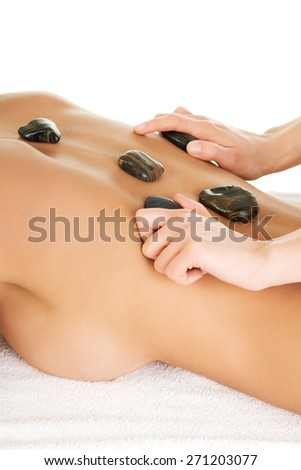 Young attractive woman getting hot stone massage. - stock photo