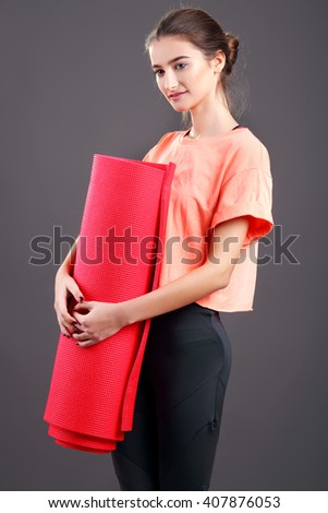 Young attractive woman holding a red yoga mat. Isolated on black - stock photo
