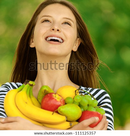 Young attractive woman holding apples, pears, grapes and bananas, against green of summer park. - stock photo