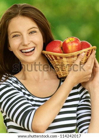 Young attractive woman holding basket with apples, against green of summer park. - stock photo