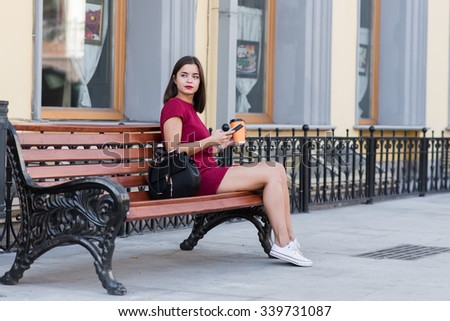 Young attractive woman holding mobile phone and cup of take away coffee while sitting alone on a wooden bench, gorgeous brunette female using cell telephone while relaxing outdoors after work day  - stock photo