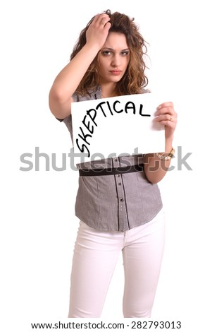 Young attractive woman holding paper with Skeptical text on white background - stock photo
