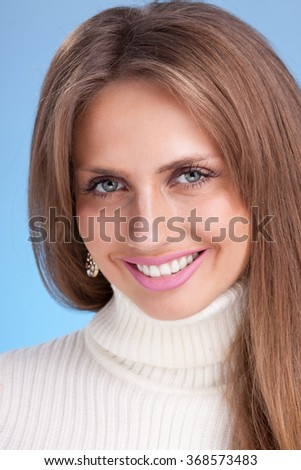 Young attractive woman in a warm sweater on blue background - stock photo