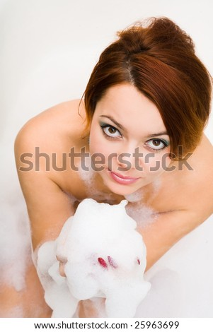 young attractive woman in bathtub with foam in hands - stock photo