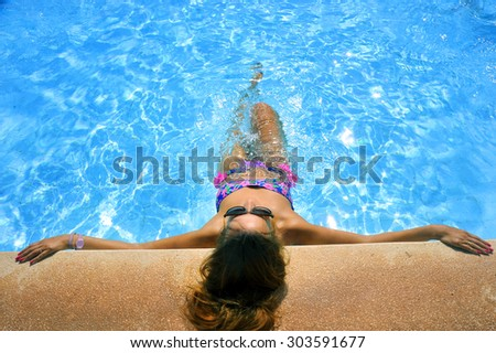 young attractive woman in bikini and sunglasses sunbathing leaning on edge of holidays resort swimming pool in comfort and relax enjoying summer vacation - stock photo