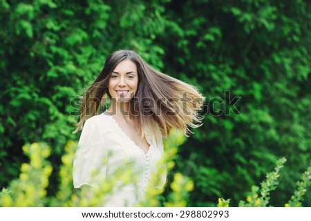 Young attractive woman in blooming spring park with her long beautiful hair streaming in the wind - stock photo