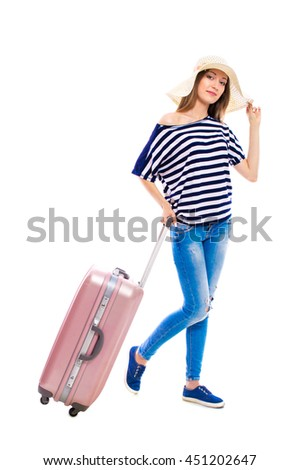 Young attractive woman in blue jeans and a hat with a suitcase isolated on white background. Recreation and tourism concept. - stock photo