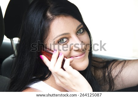 Young Attractive woman in her car, talking on her phone - stock photo