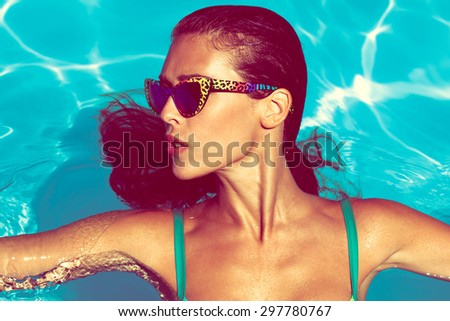 young attractive woman in  in pool with sunglasses - stock photo