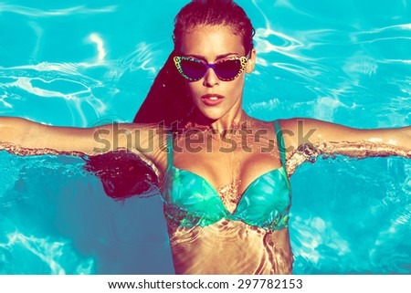 young attractive woman in  in pool with sunglasses  above view - stock photo