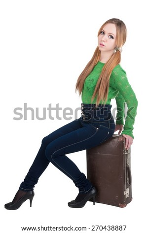 Young attractive woman in jeans and green sweater sits on old suitcase - stock photo