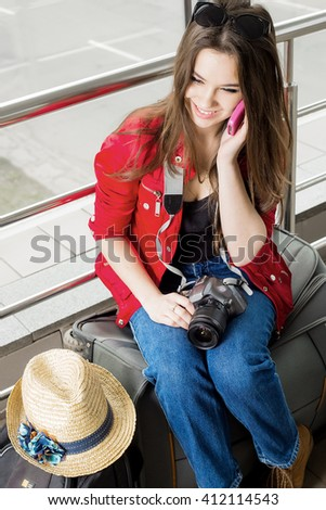 young attractive woman in red jacket sitting on suitcases in the terminal or train station and talking on the phone. The girl met on a trip. - stock photo