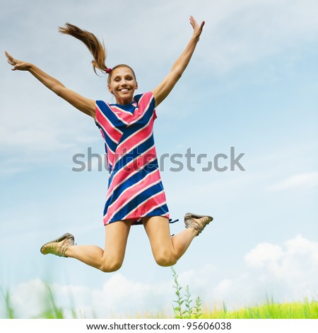 young, attractive woman in striped dress jumps up against the blue sky with clouds and green fields - stock photo