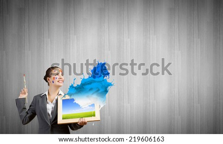 Young attractive woman in suit with paint brush in hand - stock photo