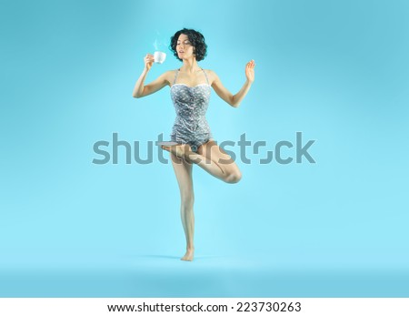 Young attractive woman in yoga asana with a cup of some hot drink. Isolated - stock photo