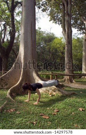 Young, attractive woman is performing a push-up next to a tree.   Vertically framed shot - stock photo