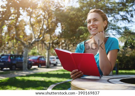 Young attractive woman is smiling for someone while is sitting with notepad in park in summer day, happy cheerful female is enjoying book and recreation time during her long awaiting spring weekend - stock photo