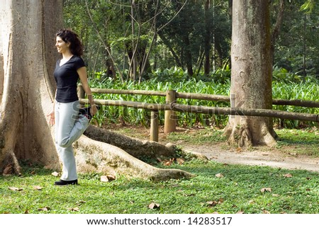 Young, attractive woman is standing next to a tree.  She is smiling and stretching her muscles.   Horizontally framed shot - stock photo