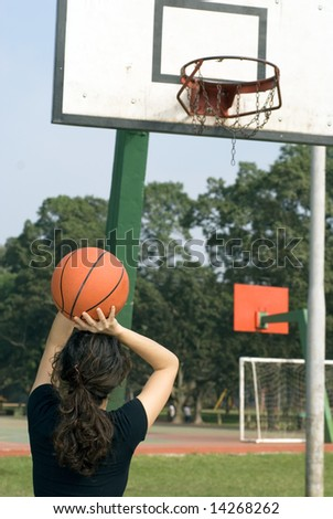 Young, attractive woman is standing on an outdoor basketball court.  She is about to shoot the basketball into the hoop.  Vertically framed shot. - stock photo