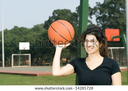 Young, attractive woman is standing on an outdoor basketball court.  She is smiling and holding a basketball up with one hand.  Horizontally framed shot. - stock photo