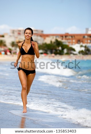 Young attractive woman jogging on the beach - stock photo