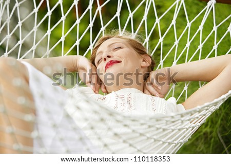 Young attractive woman laying and relaxing on a white hammock in a garden. - stock photo