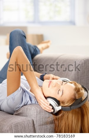 Young attractive woman listening music through headphones, laying on sofa.? - stock photo